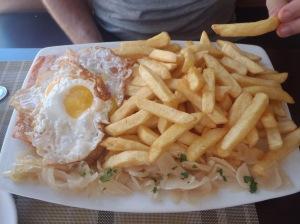 Salmão a lo pobre - um salmão gigante coberto de batata frita e ovo. Cerca de R$ 40,00 para duas pessoas